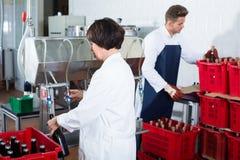 Радостный работник используя машину для того чтобы разлить вино по бутылкам Стоковое Изображение RF