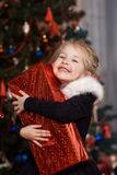 Радостный ребенок с подарком около рождественской елки Стоковое Фото