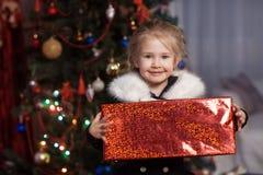 Радостный ребенок с подарком около рождественской елки Стоковая Фотография