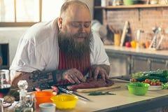 Радостный толстый мужской шеф-повар наслаждаясь приготовлением пищи Стоковые Изображения