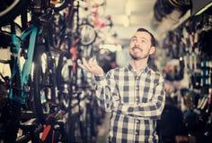 Радостный человек в магазине велосипеда выбирает для себя велосипед спорт Стоковая Фотография RF