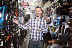 Радостный человек в магазине велосипеда выбирает для себя велосипед спорт Стоковое Изображение RF
