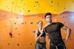 Радостный человек и женщина представляя в взбираясь спортзале Стоковая Фотография RF