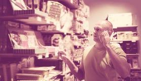 Радостный человек перед трудным выбором в магазине стоковое фото rf