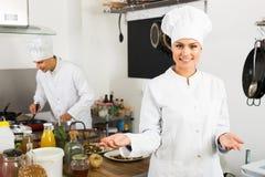 Радостный шеф-повар женщины варя еду на кухне Стоковые Изображения RF