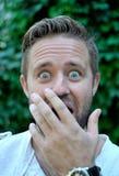 Радостный excited рот заволакивания молодого человека с рукой стоковые фотографии rf