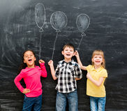 3 радостных дет держат мнимые воздушные шары нарисованный на классн классном Стоковые Изображения RF