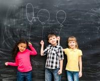 3 радостных дет держат мнимые воздушные шары нарисованный на классн классном Стоковая Фотография