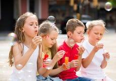 4 радостных дет дуя пузыри мыла Стоковое Изображение RF