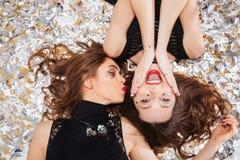 2 радостных женщины лежа на белой предпосылке с confetti Стоковые Изображения RF
