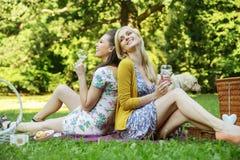 2 радостных женщины сидя на одеяле Стоковые Фото