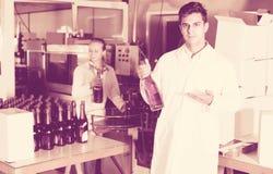 2 радостных коллеги держа бутылки вина Стоковая Фотография RF