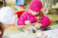 2 радостных маленькой девочки крася внешней на пасхе Стоковые Изображения RF