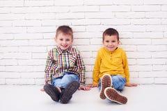 2 радостных мальчика сидя на поле и полагаясь против белизны Стоковое фото RF