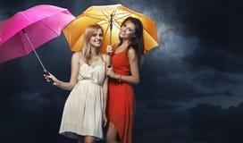 2 радостных молодой женщины с красочными зонтиками Стоковое фото RF