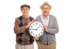 2 радостных пожилых люд держа большие часы Стоковые Изображения RF