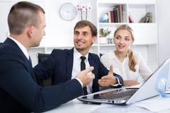 3 радостных сотрудника имея переговор стоковые изображения rf