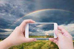 Радуга в небе над полем земледелия Стоковые Изображения