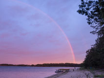 Радуга над берегом и шлюпками озера Стоковые Изображения