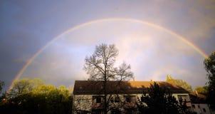 Радуга над домом с деревьями Стоковая Фотография RF