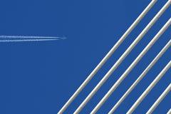 Реактивный самолет с трассировкой & белый мост на голубом небе