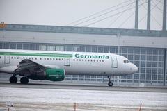 Реактивный самолет Germania в авиапорте Мюнхена, MUC, взгляде кабины, снеге Стоковое Изображение