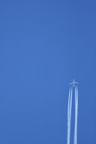 Реактивный самолет в полете выходя следы пара Стоковые Изображения RF