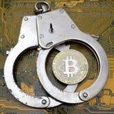 Реальная монетка bitcoin лежит на закрытых стальных наручниках против желтой доски электроники компьютера Квадратное изображение стоковое изображение
