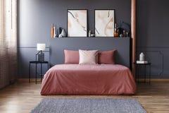 Реальное фото простого интерьера спальни с пакостными розовыми постельными принадлежностями стоковая фотография