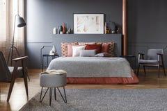 Реальное фото уютного, темного интерьера спальни с много декоративный c Стоковые Фотографии RF