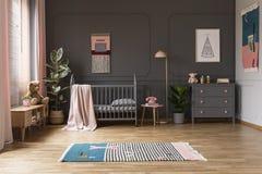Реальное фото шпаргалки младенца в сером интерьере комнаты ` s ребенка, затем стоковая фотография rf