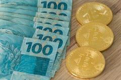 Реальные бразильские деньги и виртуальное bitcoin стоковая фотография