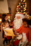Реальный отец рождества проверяя окруженный список целей с 3 g Стоковые Изображения RF