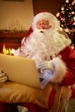 Реальный Санта Клаус используя компьтер-книжку к связывать с детьми Стоковые Фото