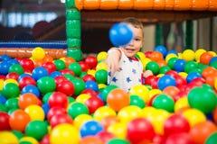 Ребенк бросая красочный пластичный шарик к камере Стоковые Фото