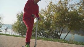 Ребенк в красной одежде едет скутер в парке Мальчик активно тратит время outdoors движение медленное видеоматериал