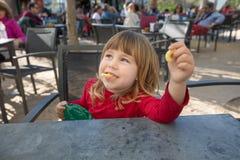 Ребенк в террасе кафа есть слойку сыра Стоковое Изображение
