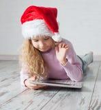 Ребенк в шляпе рождества с таблеткой Стоковая Фотография RF