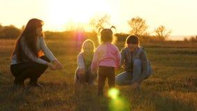 Ребенк держит футбольный мяч в лучах яркого солнца на поле Счастливая маленькая девочка играя шарик с мамой и сестрами Семья сток-видео
