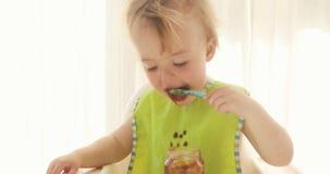 Ребенк ест пюре от черносливов и получает пакостным видеоматериал
