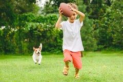 Ребенк играя американский футбол готовый для того чтобы сделать приземление и собаку гоня его стоковое изображение