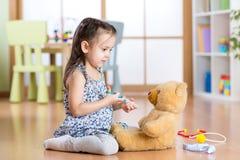 Ребенк играя доктора в комнате детей Стоковое фото RF