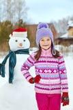 Ребенк играя с снеговиком Стоковые Фотографии RF