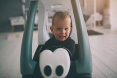Ребенк кладет на пол Мальчик играет в доме с автомобилями игрушки дома в утре Вскользь образ жизни в спальне стоковое фото
