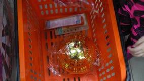 Ребенк кладет шарик для дерева Xmas в корзину для товаров в супермаркете сток-видео