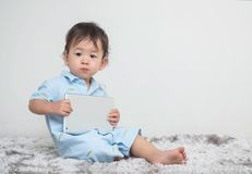 Ребенк крупного плана милый азиатский сидя с таблеткой на его руке дома на серой стене ковра и цемента текстурировал предпосылку  Стоковое Изображение RF