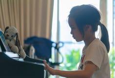 Ребенк маленькой девочки играя на ключе рояля для концепции музыки стоковые изображения rf