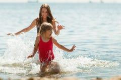 Ребенк маленькой девочки и мать женщины в морской воде Приколы Стоковые Изображения
