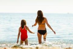 Ребенк маленькой девочки и мать женщины в морской воде Приколы Стоковое Изображение