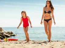 Ребенк маленькой девочки и мать женщины на пляже Стоковые Изображения RF